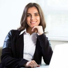Young Caucasian woman facing the camera and smiling in an office environment