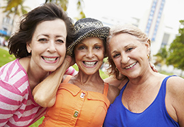 Three happy mature women smiling and looking at camera