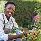 African American woman in a garden smiling outdoors