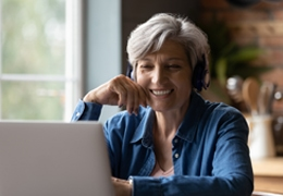 Mature Caucasian woman sitting at kitchen table with headphones on and looking at computer