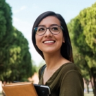 Young female Hispanic student carries books on campus
