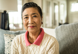 Mature woman wearing a sweater sitting on a couch smiling at camera